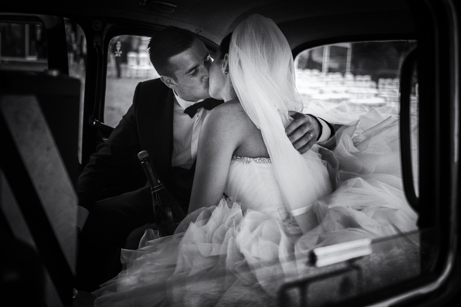 The bride and groom in the back of a london taxi at an italian wedding