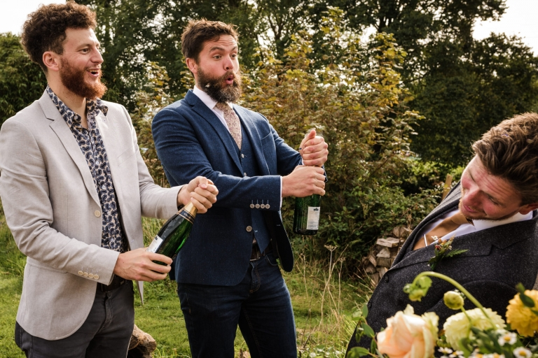 the groom dodges a champagne cork at a Cornish wedding
