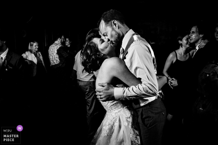 Newlywed couple kiss on the dance floor. An award winning image for unposed wedding photography.