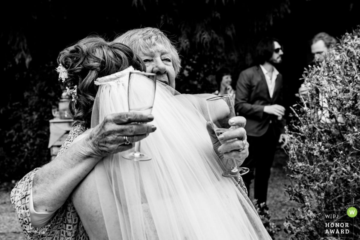 The bride and her grandmother hug at a wedding in Devon